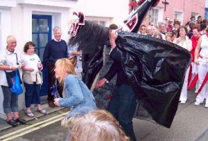 The red 'obby 'oss capturing a passing maiden during the Padstow Mayday festival