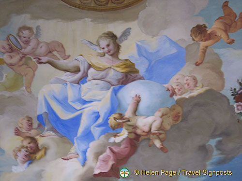 In the center of the ceiling is a female figure. She is the allegory of Faith