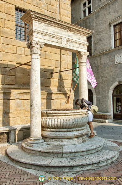 Me, peering down the ancient well in Piazza Pio II