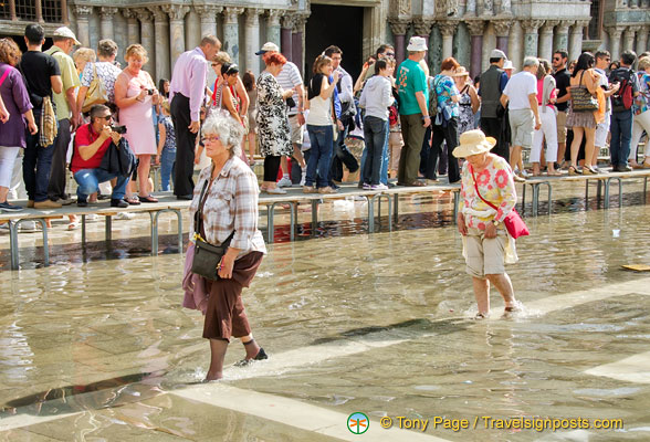 These two elderly ladies don't mind walking in the water