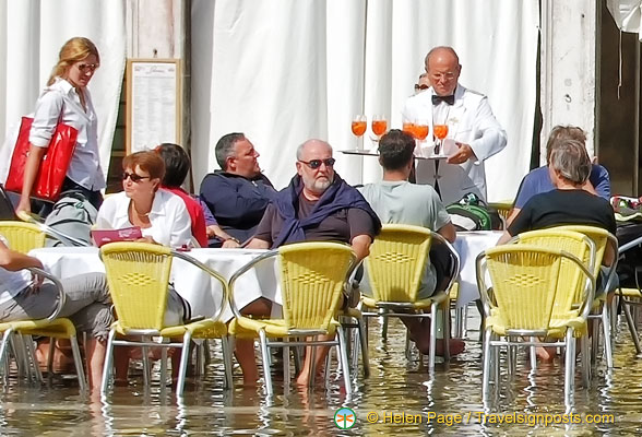 With feet in water, these tourists are enjoying drinks at the Cafe Lavena