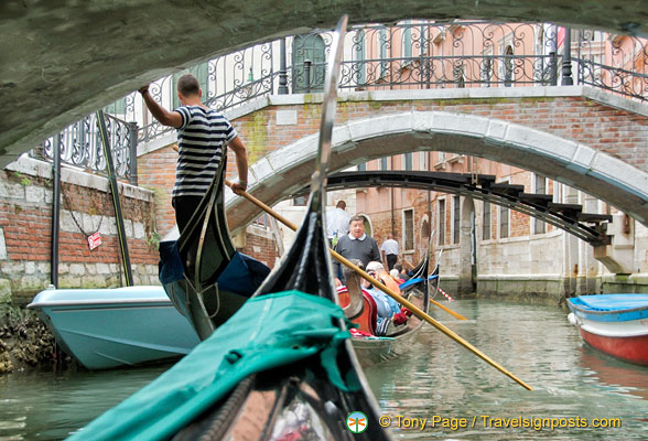 The skillful gondolier navigates under the many bridges