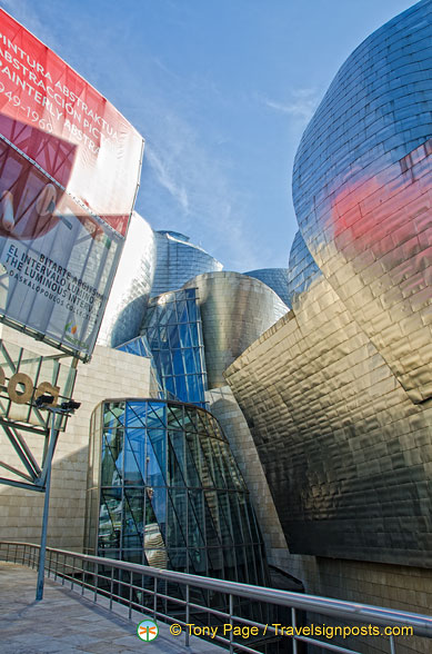 Guggenheim Bilbao's Titanium catches the red and blue of nearby structures