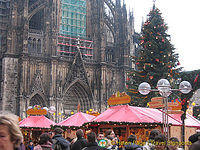 A busy Christmas market set against Cologne Dom and its Christmas tree