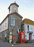 The towering Mousehole harbour office with the Post Office next to it