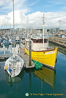 An attractive yellow wooden boat in Sutton Harbour Marina