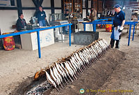 Neat rows of steckerlfisch being grilled