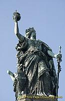 Germania holds the imperial crown in her raised right hand and the imperial sword in her left