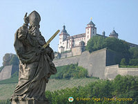 Statue of St Kilian and his golden sword with the Marienberg Fortress in the background
