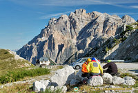 Three travellers checking their bearings on Passo Valparola