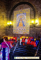 Pilgrims leave candles as offerings to Our Lady on exiting the Niche
