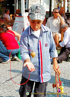 Young vendor selling spinning tops to tourists